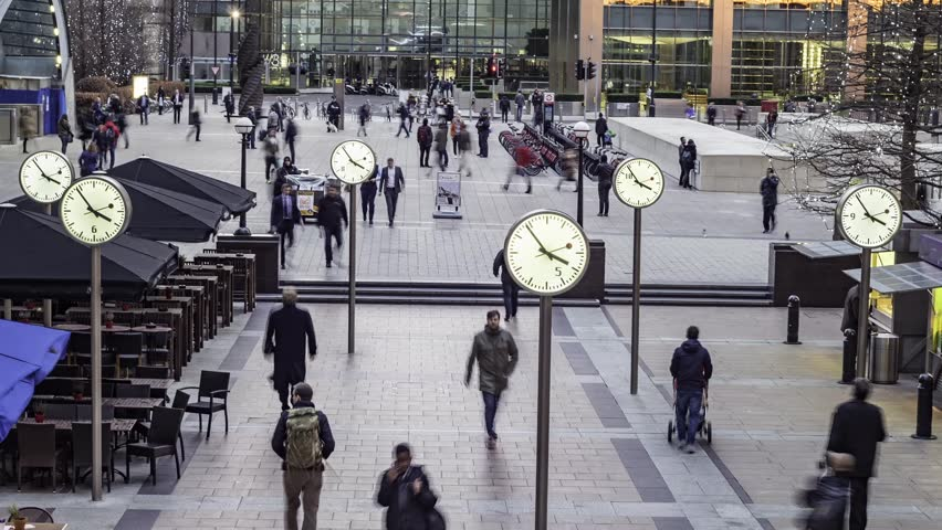 Timelapse of people rushing from work with several clocks in the docklands financial centre in London #13784033
