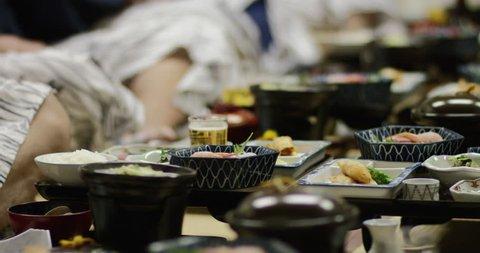 Hokkaido, Japan - Japanese dinner traditional Hokkaido eat sushi raw fish traditional dinner after ski rice bowl sit low table after ski onsen bath robe. Hokkaido, Japan February 2016.