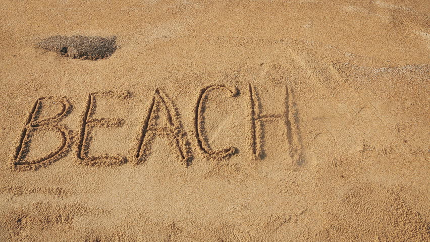 word beach appearing letter by letter followed by an arrow on a sandy beach letters