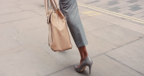 Beautiful mixed race business woman's feet power walking through city in high heels