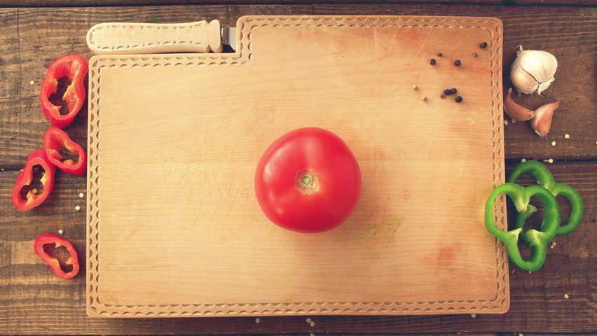 Tomato quickly being diced on wooden board top down view UHD 4K proresHQ