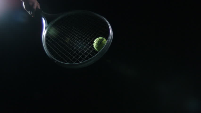 EXTREME SLOW MOTION Tennis racket hits ball up into sky against black background. #13873403