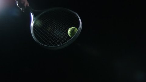 EXTREME SLOW MOTION Tennis racket hits ball up into sky against black background.