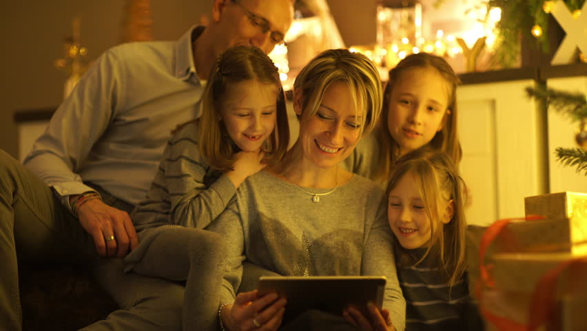 4k footage, medium shot parents with three girl children smiling and looking into digital tablet at home on christmas eve, captured with atomos shogun  | Shutterstock HD Video #13880153