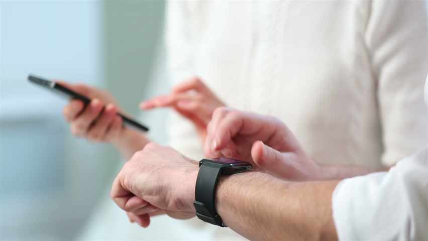 A man uses a smart watch but the woman uses smartphone. Close-up. | Shutterstock HD Video #13908800