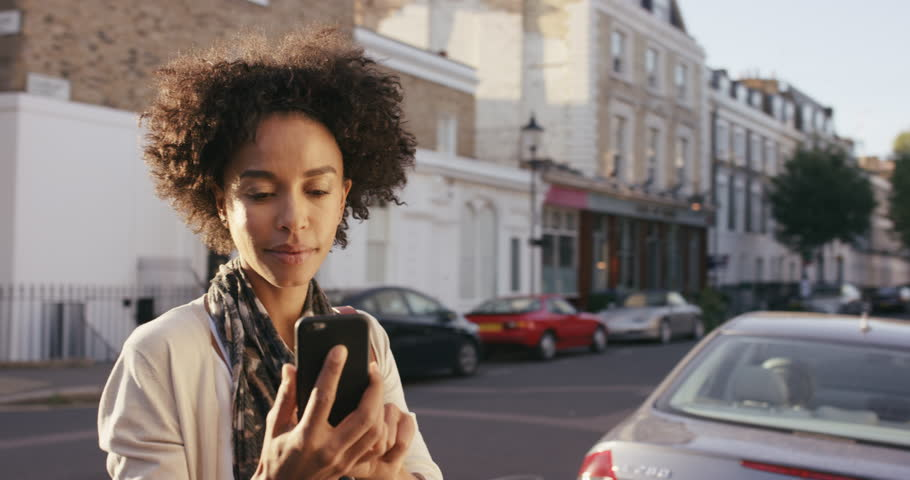 Beautiful Mixed race woman using smart phone technology app walking through city streets living urban happy lifestyle