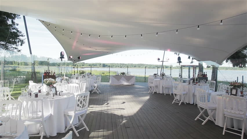 Everything is set and ready for the wedding party in an outdoor restaurant. Wedding reception decoration with all white on summer terrace near the lake. Flycam | Shutterstock HD Video #13926713