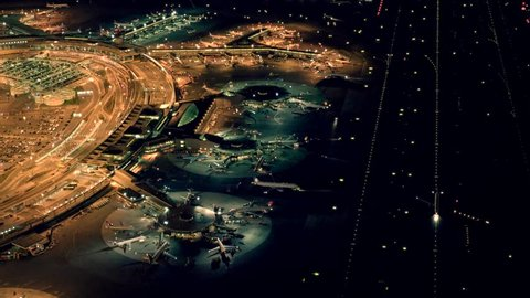 helicopter establishing shot of airplanes parking at international airport terminal at night. global business background