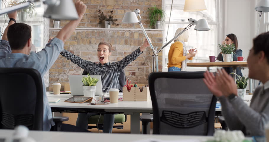 Business woman with arms raised celebrating success watching sport victory on laptop diverse people group clapping expressing excitement in office