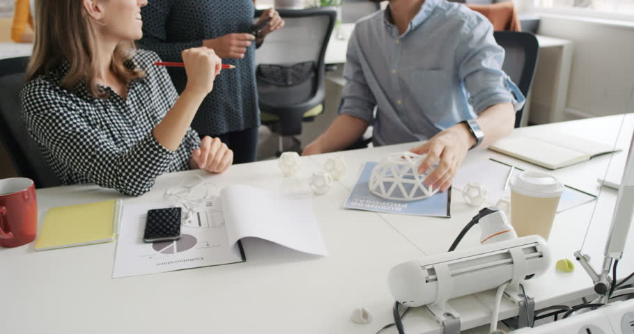 Business woman using tablet app showing 3d printed model of geodesic dome walking through modern office to diverse team meeting