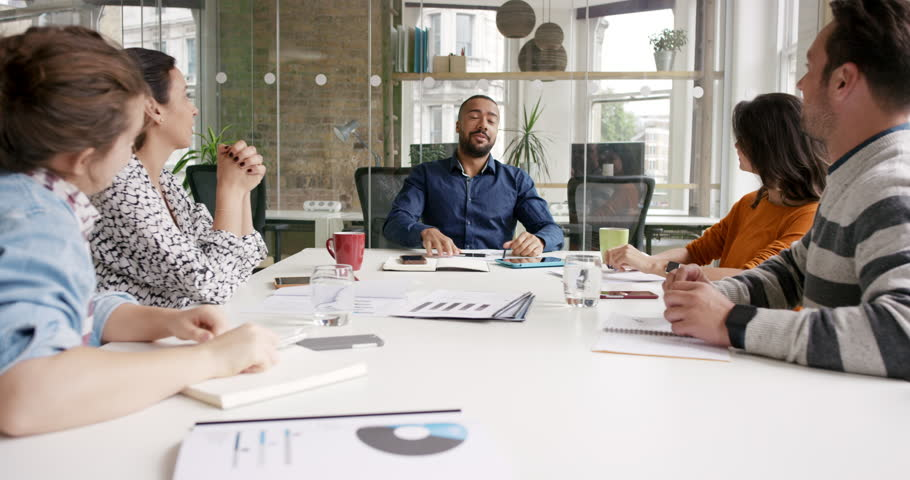 Diverse business people clapping in Creative team meeting celebrating success in casual modern office boardroom with natural light and large open windows