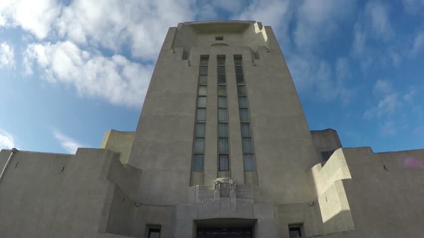 Footage camera tilt up of an old abandoned communication building art deco style architecture grey white building looks like modern church or cathedral camera tilt front of main tower 4k resolution