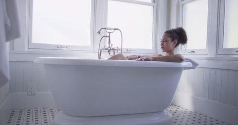 Beautiful young mixed race woman taking a bath