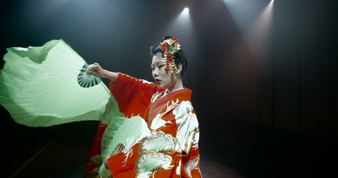 beautiful Japanese geisha posing for the camera with fans on stage, epic slow motion, smoke and dark background