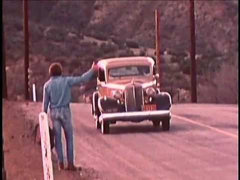 Rear view of man with briefcase hitchhiking on country road, 1970s