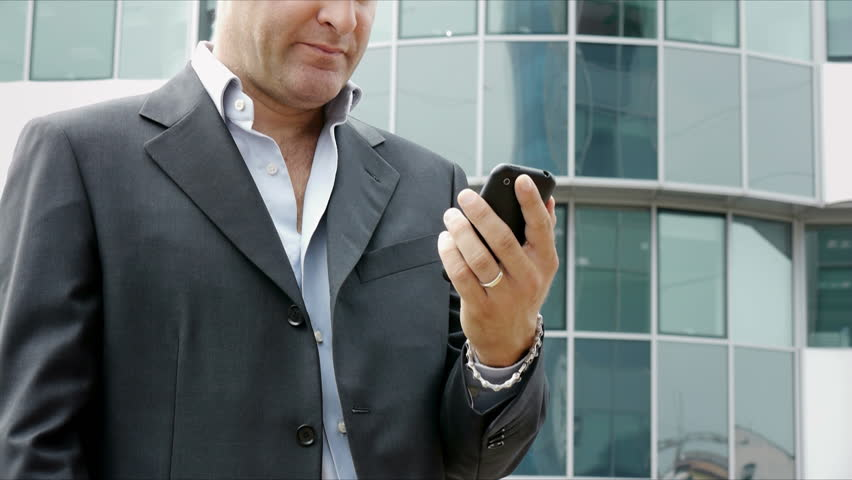 Happy businessman with mobile telephone or smartphone, visiting web site and browsing the internet