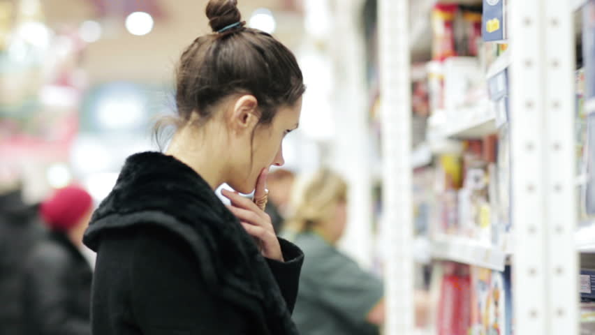 Girl selects the item on the shelves in the store  | Shutterstock HD Video #14039543