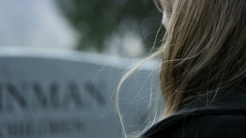 slow motion somber girl leaving rose on gravestone in cemetery