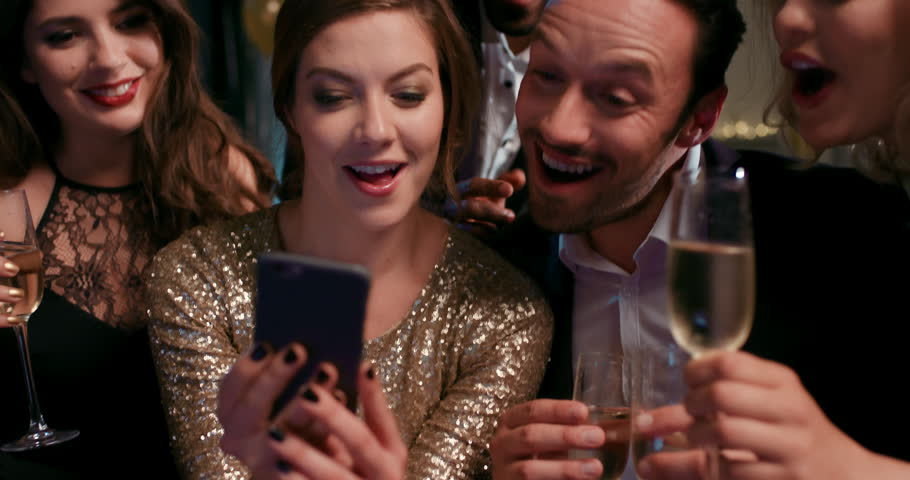 Sexy friends laughing at funny viral video online watching social media on smart phone at glamorous fashion party drinking champagne | Shutterstock HD Video #14075978