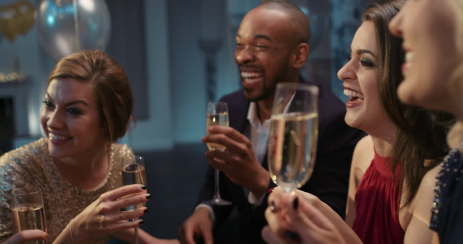 Friends holding up champagne flutes together in a toast at sexy glamorous party celebration cheers   Shutterstock HD Video #14076083