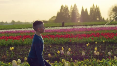 Slow motion portrait of young boy running and frolicking in a field of tulips at sunset