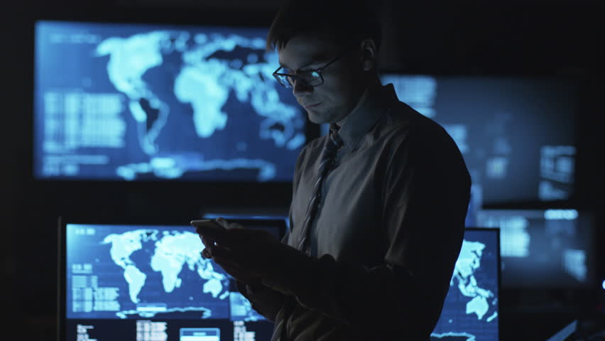 Man in glasses is using a smartphone in a dark monitoring room filled with display screens. Shot on RED Cinema Camera in 4K (UHD). | Shutterstock HD Video #14097563