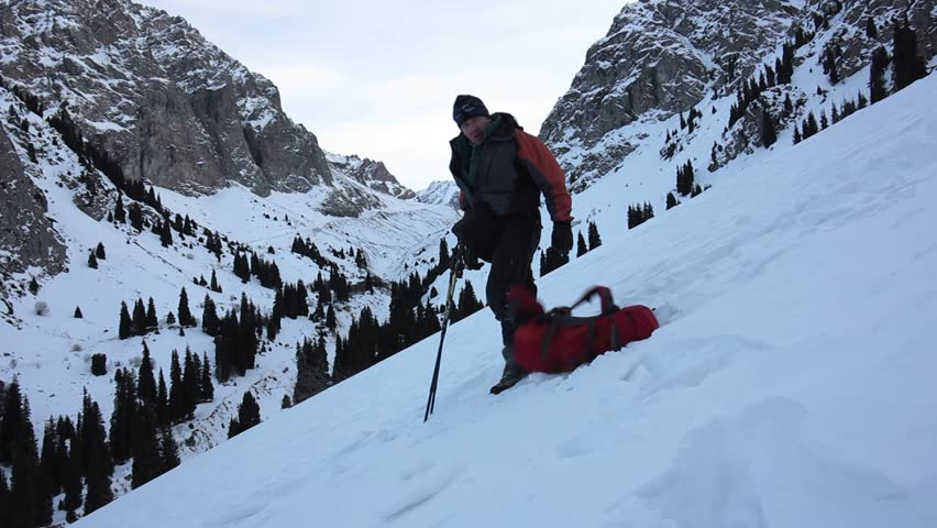 Tourist sat down to rest on his backpack on a snowy mountain trail  | Shutterstock HD Video #14123063