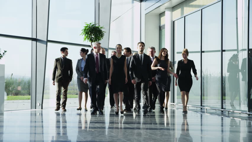 4k / Ultra HD version Portrait of an attractive multi-racial business team, as they walk through a light and modern glass fronted office building towards the camera. In slow motion. Shot on RED Epic