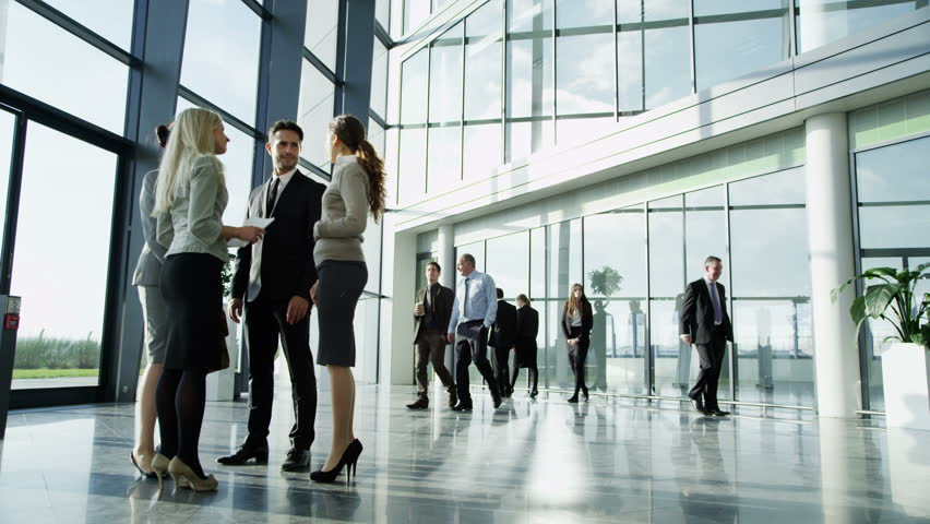 4k / Ultra HD version An attractive young business team are having a conversation in a bright modern office building. Other workers in the building walk past them. In slow motion. Shot on RED Epic | Shutterstock HD Video #14126996