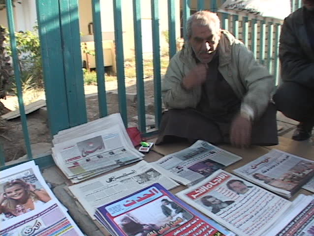 IRAQ - CIRCA 2003: An Iraqi vendor shows a newspaper with headlines of Saddam Hussein's capture circa 2003 Iraq.
