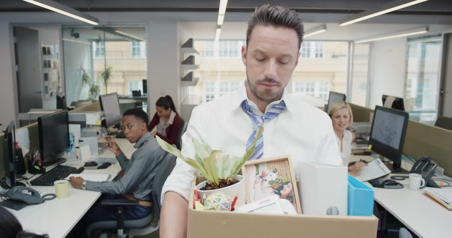 Businessman getting fired carrying box of personal belongings being made redundant in recession sad worried failure | Shutterstock HD Video #14142869