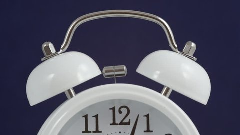 A classical analog quartz alarm clock starts to ring