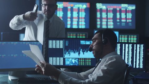 Team of stockbrokers are having a discussion in a dark office with display screens. Shot on RED Cinema Camera in 4K (UHD).