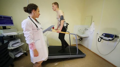 Female doctor monitors the progress of the a young man EKG during physical activity