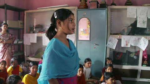 Baruipur, India - CIRCA 2013 - Girl stands and recites in classroom