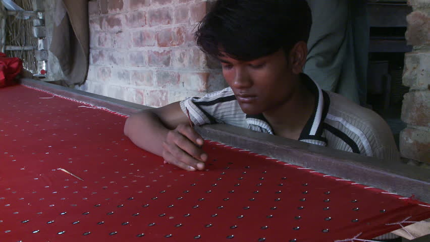 Baruipur, India - CIRCA 2013 - Close up view of mans hand sewing sequins on fabric