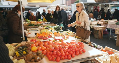 STRASBOURG, FRANCE - CIRCA 2016 Mature woman buying tomatoes as people with diverse ethnicities are buying fruits and vegetables in a street market on a typical French Market in the city of Strasbourg