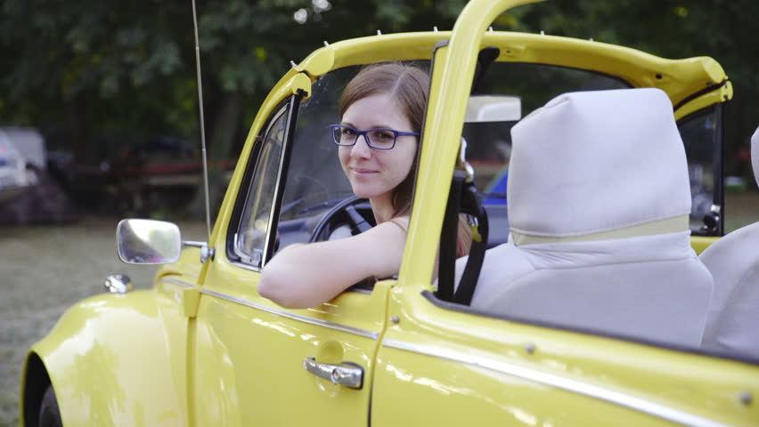 Woman smiling from a yellow retro car 4K. Attractive female person with glasses smiling while leaned on cabriolet door and looking back.
