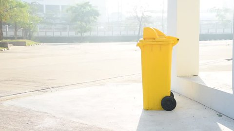Boy carry garbage bag and drop in the yellow bin
