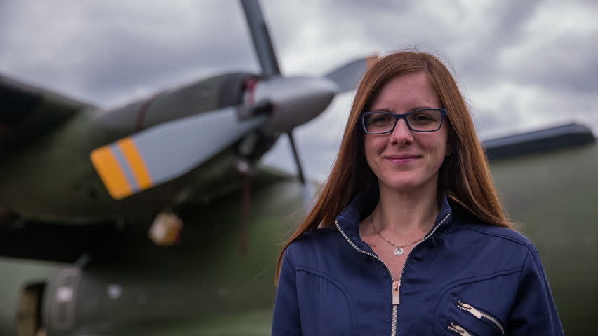 Woman pilot portrait in front of bomber plane. Young attractive female person with long brown hair and in blue jacket standing in front of huge aircraft propellers in background.