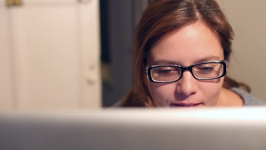 Girl with glasses smiling and having fun on the computer, dolly shot. Young woman smiling and having fun on the computer - 1080p | Shutterstock HD Video #14262923