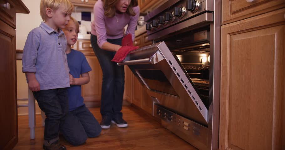 Lovely mother opens baking oven door for cookies