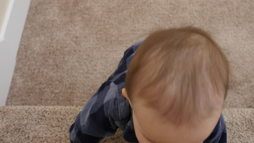 A gimbal shot of a little baby boy learning to crawl up the stairs in his home