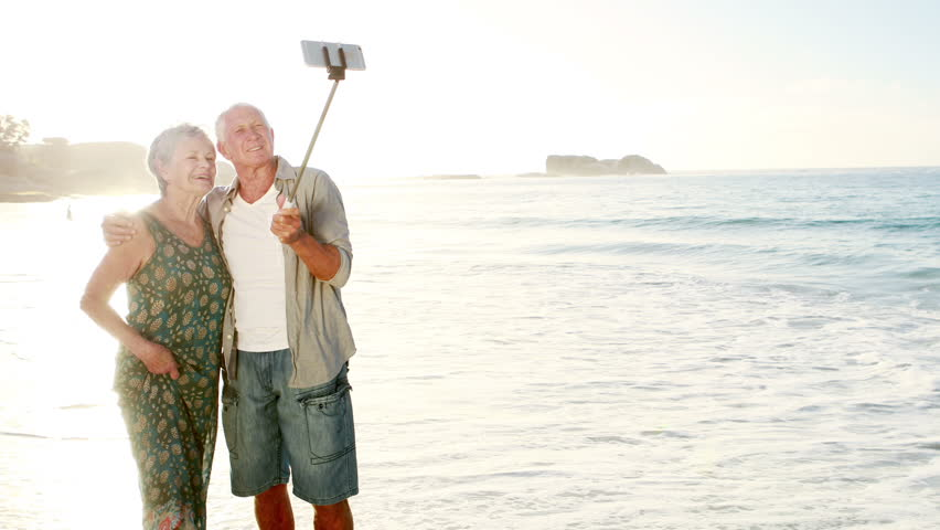senior couple taking a selfie from selfie stick on beach stock footage video 21423487 shutterstock. Black Bedroom Furniture Sets. Home Design Ideas