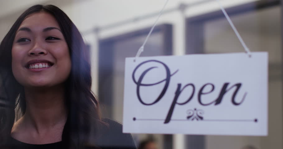 """A beautiful woman proudly turns over an """"open"""" sign in her shop window. Shot on RED Epic in slow motion."""
