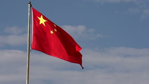 Waving Chinese Flag. Flag of the People's Republic of China against the blue sky with white clouds. Slow Motion at a rate of 240 fps