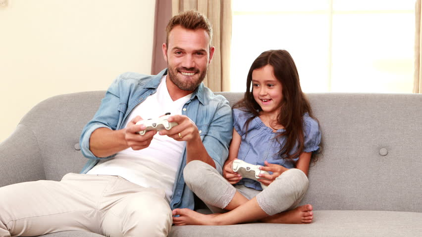 Happy Father And Daughter Playing Video Games On The Sofa