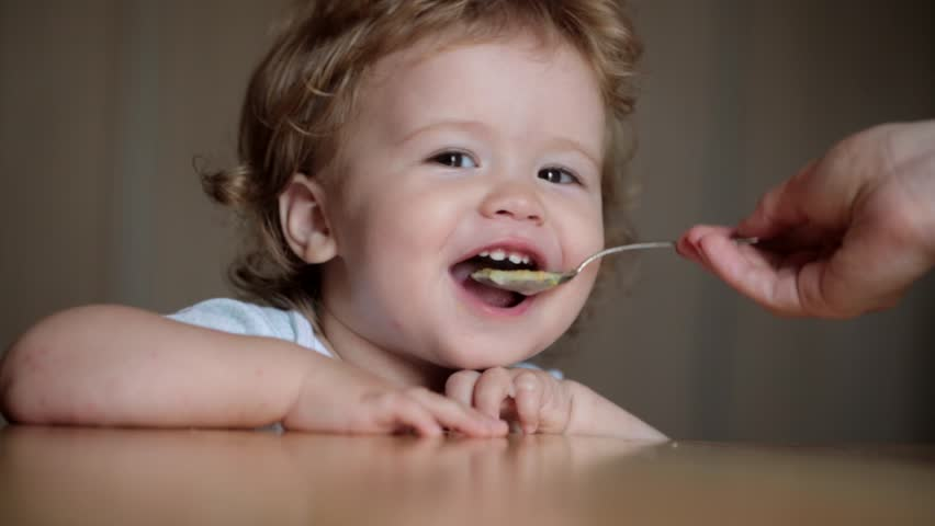 Cute little baby feeding with a spoon at the table, boy eating solid foods | Shutterstock HD Video #14380744
