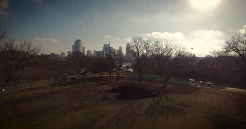 The camera flies over Zilker Park at a low altitude, then gains altitude to reveal Lady Bird Lake in Austin, Texas.  Paddle boarders are seen on the water.