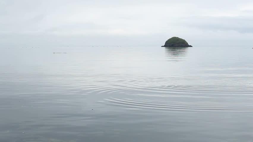 Flat, smooth stone tossed into water ripples across surface towards green, jutting boulder off coast of Kodiak Island, Alaska. 1080p